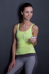 young beautiful sporty woman listening music with phone over gre