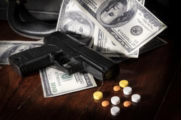 Gun and drug pills on dollar bills.