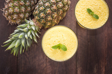 Top pineapple smoothie on wooden table