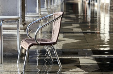 chair at high tide under the arcades during the flood in Venice