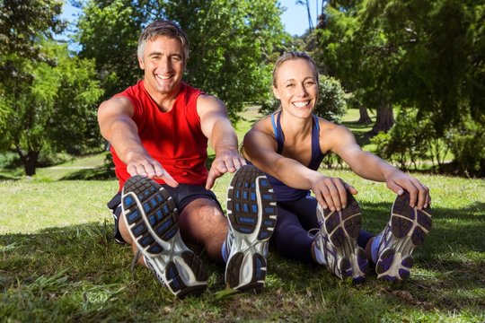Fit couple stretching in the park