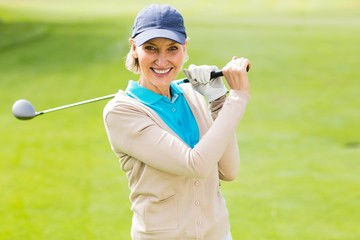 Female golfer taking a shot and smiling at camera