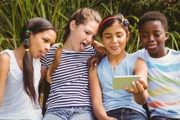 Happy children taking selfie at park