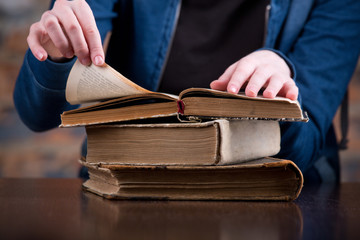 A woman two hands hold a open book spread.