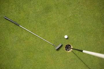 Golf club and golf ball on the putting green beside flag