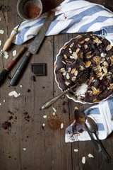 homemade dark chocolate and almonds cake on wooden table