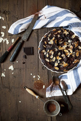 homemade whole dark chocolate and almonds cake on table