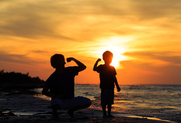father and son comparing arm strength at sunset