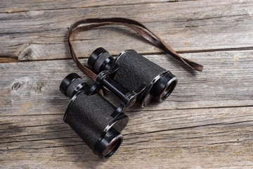 vintage binoculars on wooden background