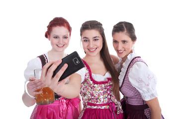 Freundinnen in Dirndl machen Selfie mit Smartphone