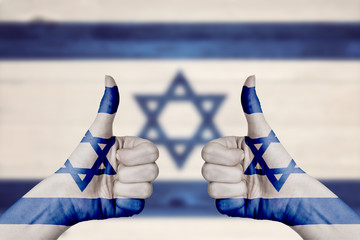 Israel flag painted on female hands thumbs up