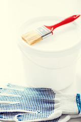 paintbrush, paint pot and gloves