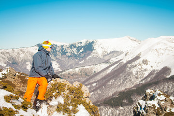 Skier sportsman at mountain cliff with a panoramic background