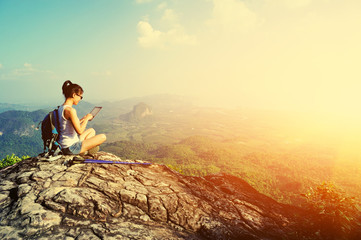 young woman hiker use digital tablet at mountain peak