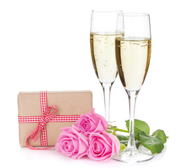 Two champagne glasses, gift box and pink rose flowers