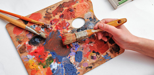 Artist's hand with brushes and palette of colors