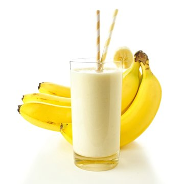 Banana smoothie in a glass with straws over white