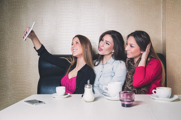 Three young girls taking selfie in a cafe