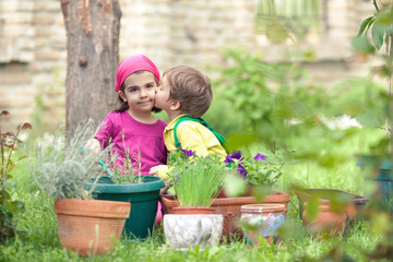 Little boy giving a kiss to his sister while playing in a garden