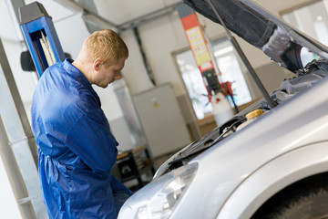 Man worker at car service during vehicle repairing works