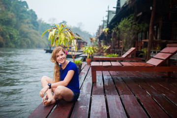 happy young woman at beach house on the River Kwai in Thailand