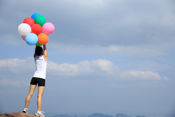 young asian woman mountain peak  with colored balloons