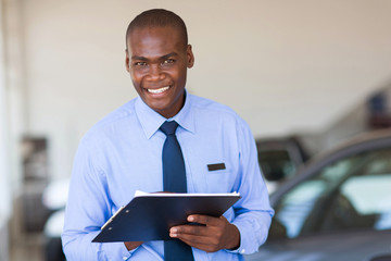 african salesman working at vehicle showroom