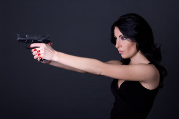 young sexy woman shooting with gun over grey