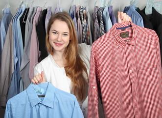 Mitarbeiterin in Wäscherei präsentiert zwei Hemden den Händen