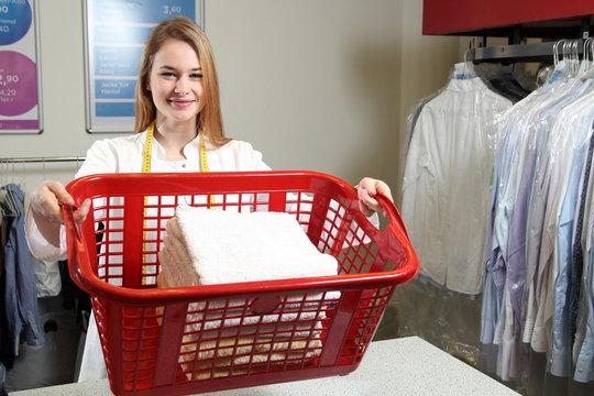 Mitarbeiterin in Wäscherei mit Wäschekorb