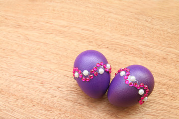 purple eggs on wooden background