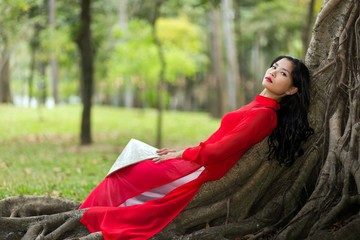 Pretty Vietnamese lady relaxing on tree roots