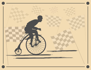 The young man quickly rides a bicycle on a background of flags