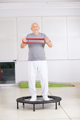 Alter Mann mit Gymnastikband auf Trampolin