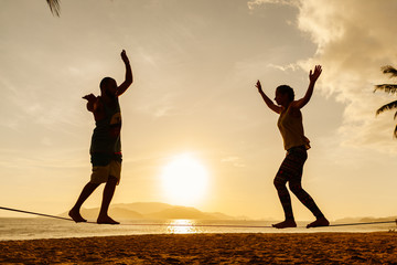 teenage couple balancing slackline on the beach