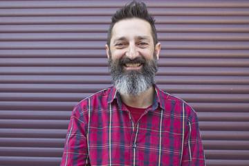 Bearded man smiling maroon wall
