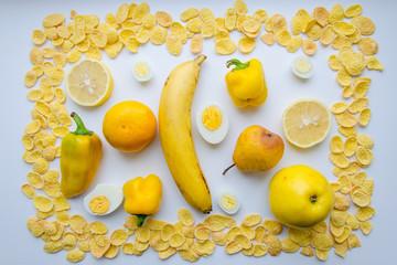 Картина из еды в желтом цвете на белом фоне