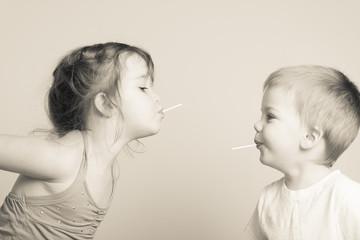 siblings having fun with lollipops
