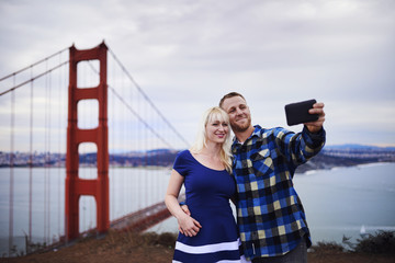 romantic couple taking selfies in front of golden gate bridge