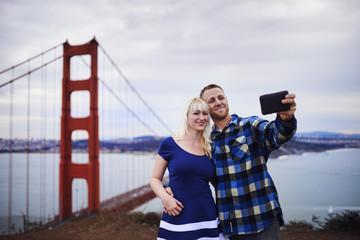 romantic couple taking selfies in front of golden gate bridge
