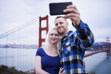 couple taking selfies in front of golden gate bridge