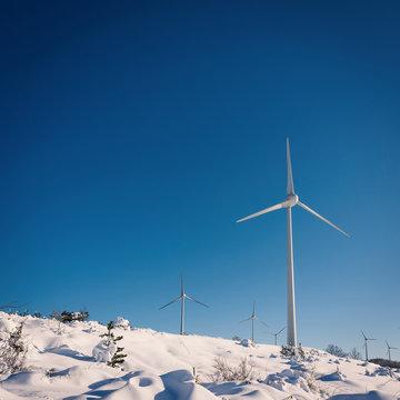 Wind turbines on snow winter landscape with dark blue sky.