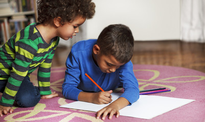 Young mixed race boys drawing on paper with crayon.