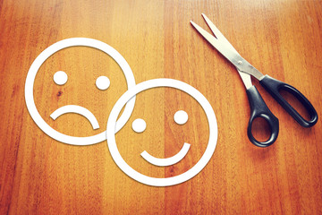 Sad and happy emoticons made of paper on the desk
