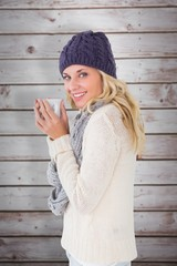 Composite image of pretty blonde in winter fashion holding mug