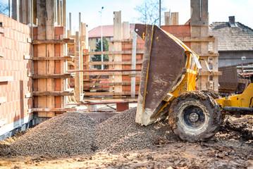 industrial truck unloading gravel with excavator