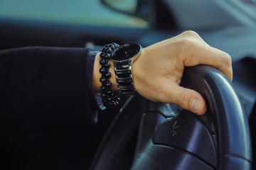 Color image of adult male hand with watch and bracelet in car