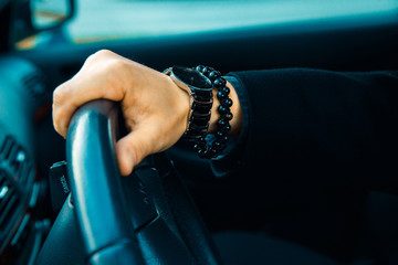 High contrast picture of male hand with watch and bracelet in ca