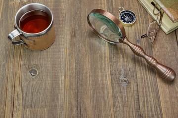Compass, Magnifying Glass, Tea Mug, Two Notebooks on Wood Table