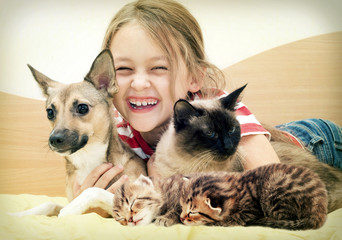 laughing child and a cat and a dog